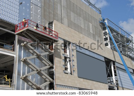 A Scissor Lift Platform and a cherry picker on a construction site - stock photo