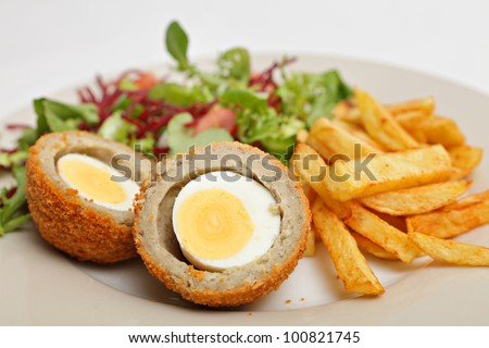 A Scotch egg - a hard boiled egg wrapped in breaded sausage meat and deep fried - served with chips (french fries) and a salad of lettuce, tomato and grated beetroot