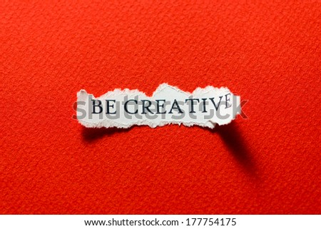 A scrap of paper with the motto, be creative - stock photo
