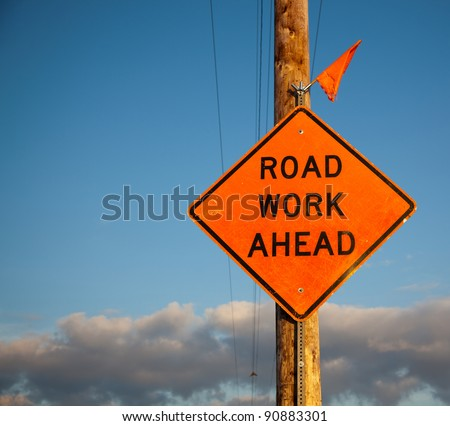A scratched orange road work ahead sign with one tattered flag on top is bolted to a roadside power and telephone pole with a blue sky background. - stock photo
