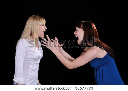 a screaming mad woman reaching out to grab another woman - stock photo