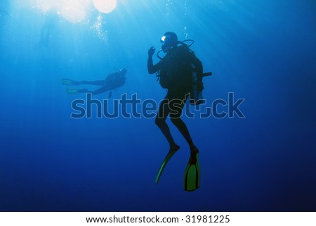 A scuba diver decompressing after dive. Surrounding waters are serene and penetrated by sun beams. - stock photo