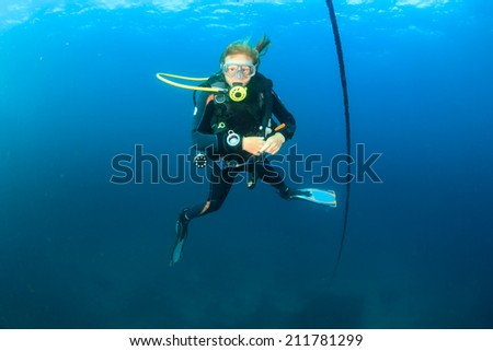 A SCUBA diver hovers next to a line in blue water - stock photo