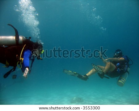A scuba instructor guides a student - stock photo