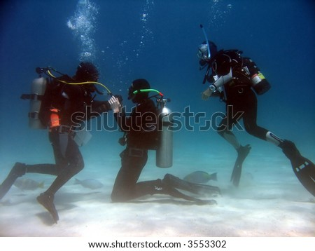 A scuba student practicing taking air from the instructor while another student watches. - stock photo