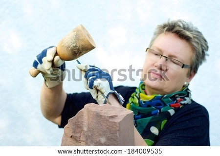 A sculptor processes a sandstone - stock photo