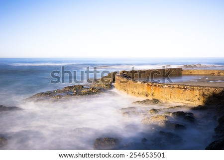 A sea wall lit by a morning sunrise protects a small, enclosed sandy beach from oncoming waves as they crash and splash high into the air. - stock photo