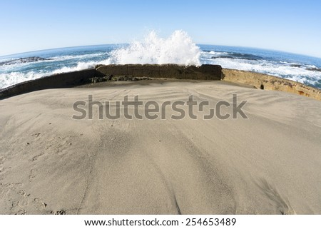 A sea wall protects a small, enclosed sandy beach from oncoming waves as they crash and splash high into the air. - stock photo