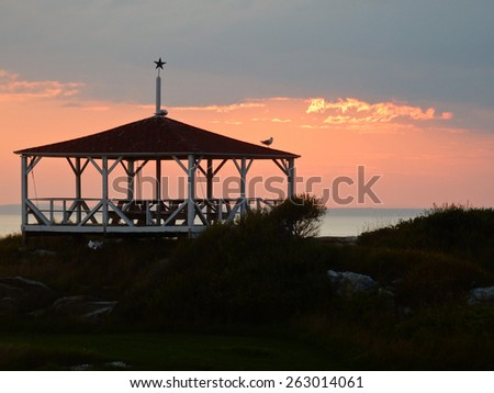 A seagull perches atop an old wooden gazebo as the sun sets in the distance. - stock photo