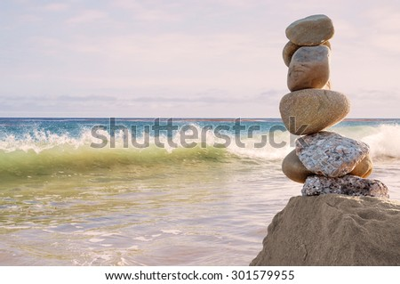 A seascape featuring a column of balanced rocks and a breaking wave overlooking the Pacific ocean at sunset.   - stock photo