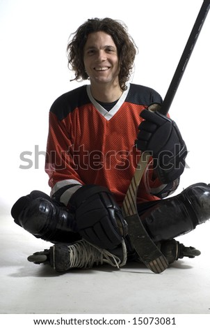 A seated hockey player smiling at the camera. Vertically framed shot. - stock photo