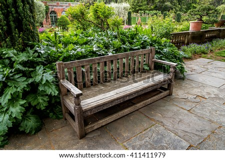 A secluded old English garden style park bench, is surrounded by lush green plants, vegetation, and shaded by a century old tree. In the background, an old brick English mansion from the 20th century. - stock photo