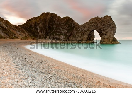 A 30 second exposure of the sunrise at Durdle Door on the Jurassic Coast in Dorset, UK. - stock photo
