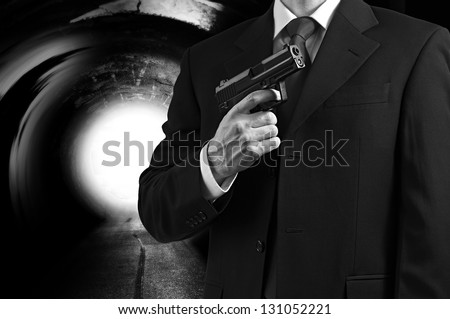 A secret agent holding a gun against a tunnel background with a bright light.