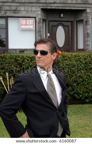 a secret agent wears dark sunglasses and a dark suit while he looks around to protect his employer while at a high profile event - stock photo
