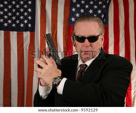 a Secret Service Agent holds his weapon at the ready position - stock photo