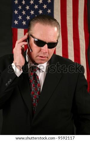 a Secret Service Agent speaks on his ear piece - stock photo