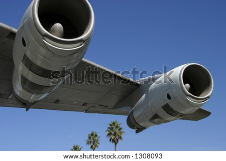 A section of a jumbo jet, viewed from below, with palm trees trailing behind. - stock photo