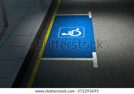 A section of a tarmac road with an empty demarcated paraplegic parking area at night lit by a street pole light - stock photo