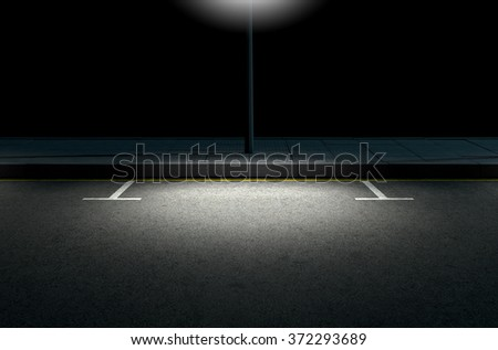 A section of a tarmac road with demarcated parking areas next to a pavement lit by a street pole at night