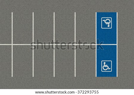 A section of an empty parking lot with an empty demarcated paraplegic parking area - stock photo