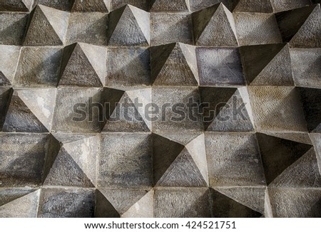 A section of an exterior wall shows an architectural detail of pyramids carved in stone in a repeating geometric pattern.