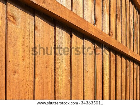 A section of brown, vertical, overlapped wooden garden fence in closeup in the sun with shadows - stock photo