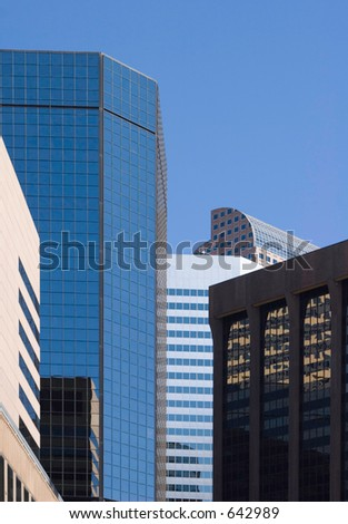A section of Denver's skyscape with tall glass and brick buildings mirroring each other.  Several geometrical shapes intersecting. - stock photo