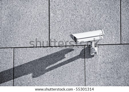 a security camera on a wall - stock photo