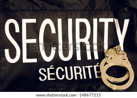 A security guards vest with the word Security in both enlgish and french, with a pair of handcuffs sitting on it. - stock photo