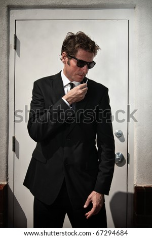 A security man talks into his wired microphone while standing guard in front of a door in a shadowy area