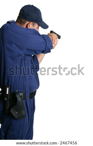 A security officer stands and aims his weapon while on duty or during weapons training. - stock photo