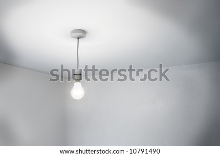 A seedy corner of a room lit by a single bare lamp - stock photo