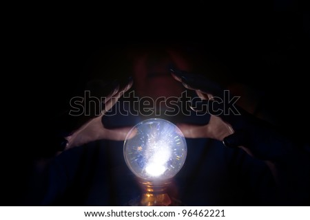 A seer working over a glowing crystal ball, foretelling the future. - stock photo