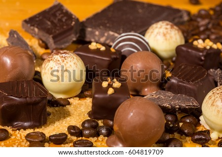 chocolate truffle pralines decorated on a wooden table with dark ...