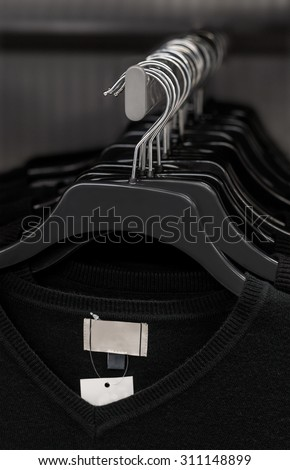 A selection of black V-neck shirts hanging on a clothes rail by coat hangers. The identical shirts are all new with labels attached. - stock photo