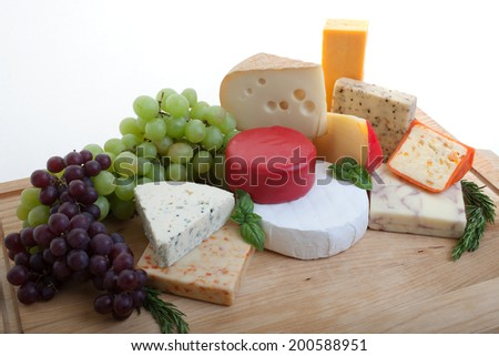 a selection of cheeses and grapes on wood with fresh herbs