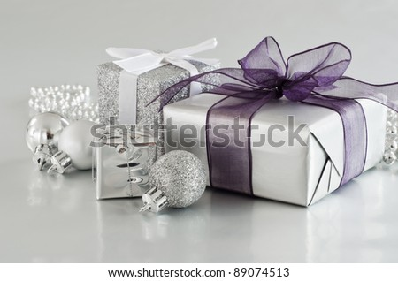 A selection of Christmas gifts and ornaments in silver, on a silver reflective surface. - stock photo