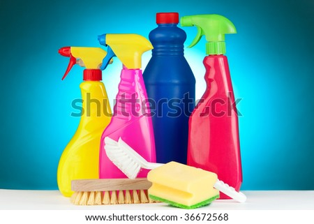 A selection of colorful cleaning equipment on a blue background. - stock photo