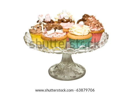 A selection of fancy homemade cupcake on glass pedestal cake stand. - stock photo