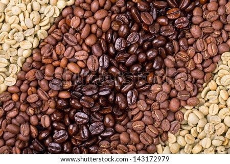 A selection of fresh roasted and unroasted coffee beans arranged in a diagonal stripe pattern. - stock photo