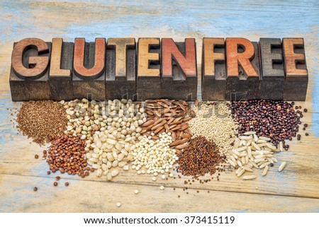 a selection of gluten free grains (quinoa, rice, teff, buckwheat, sorghum,kaniwa, amaranth) and text in vintage letterpress wood type printing blocks against painted wood - stock photo