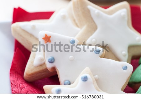 A selection of iced and decorated Christmas biscuits, in tree and star shapes. Plated with a red napkin.