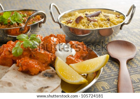 A selection of Indian food, including chicken tikka masala with chapati, pilau rice and keema matar (mince with peas). - stock photo