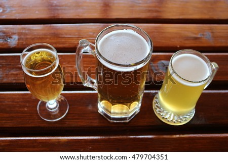 A Selection Of Lager, Cider And Wheat Beer In Differently Shaped Glasses On  A Wooden