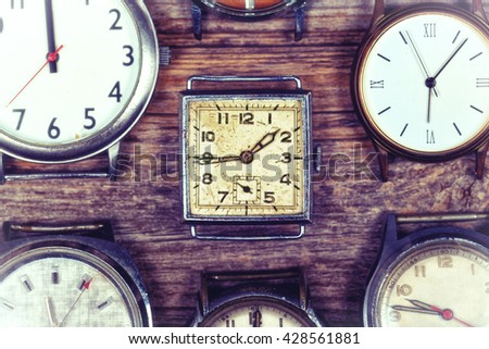 A selection of retro and antique watches over old wood background. Filtered to look like an aged instant photo. - stock photo