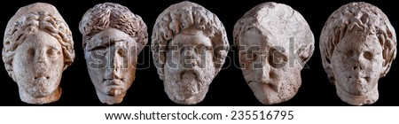 A selection of Roman statue heads isolated against a black background. - stock photo