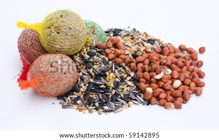 a selection of seeds, nuts and fat balls to feed wild birds on white