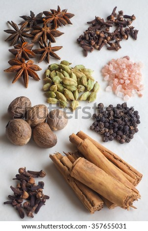 A selection of spices - cloves, cinnamon bark, black pepper corns, whole nutmegs, cardamom pods, star anise - with pink rock salt crystals. - stock photo