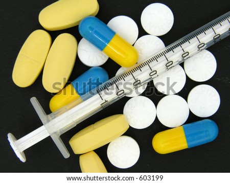 A selection of tablets and pills with a syringe laying over the top all on a black background.